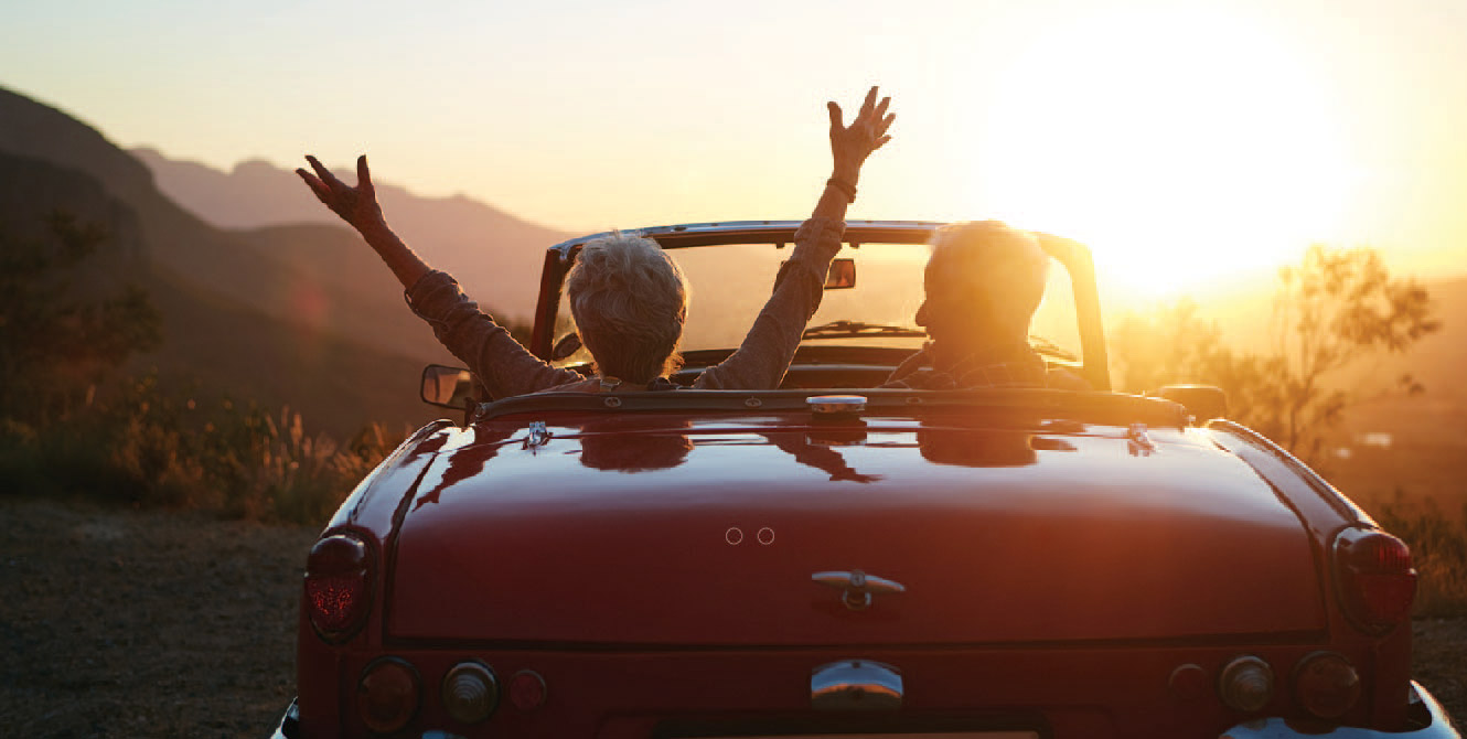 Retired couple enjoying a sunset in their sports car.