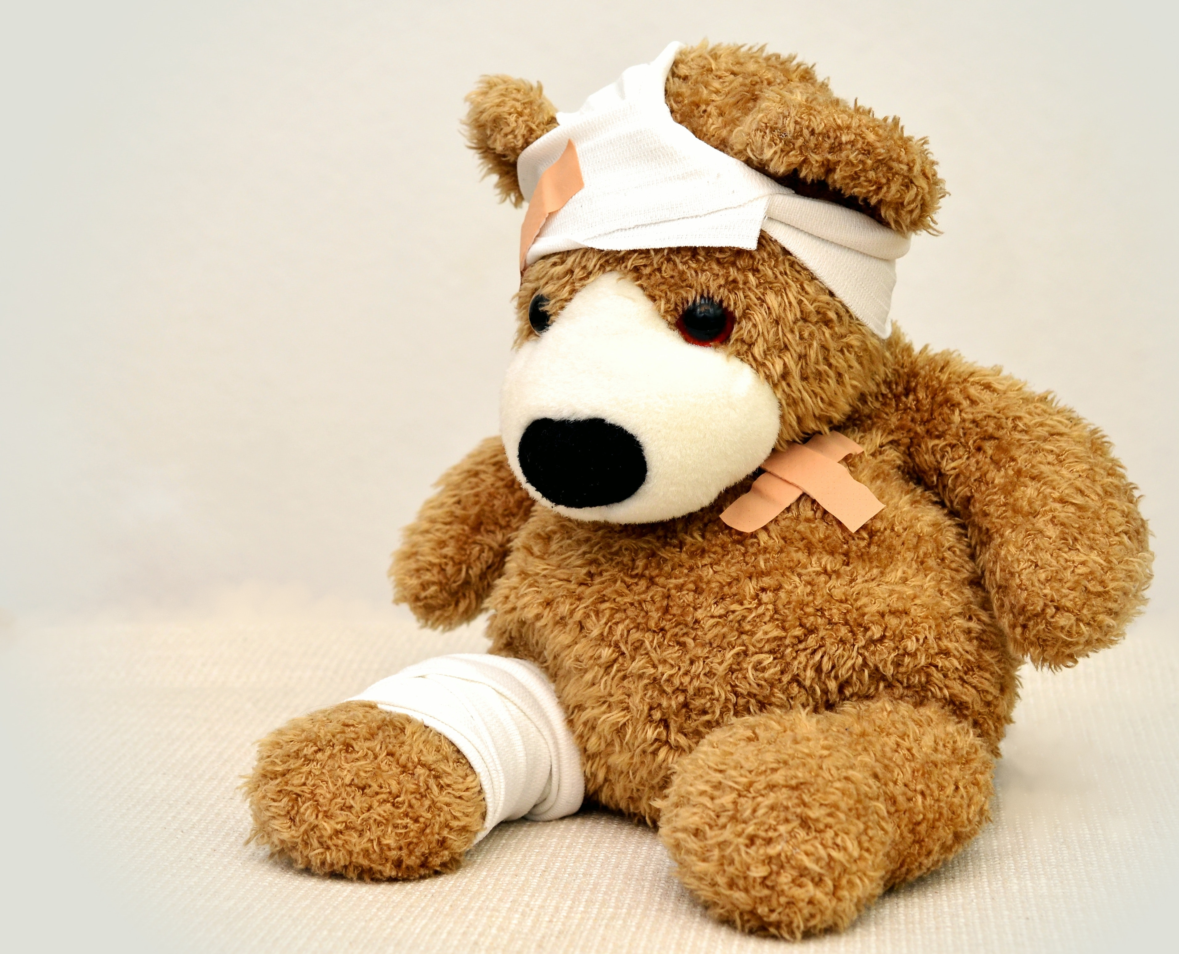 brown plush bear with bandages